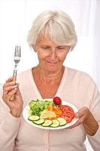 пожилая женщина ест овощи