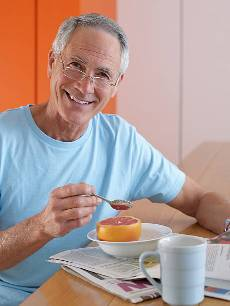 пожилой человек ест грейпфтрут